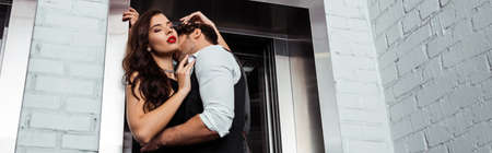Panoramic crop of man kissing and hugging beautiful woman near elevator