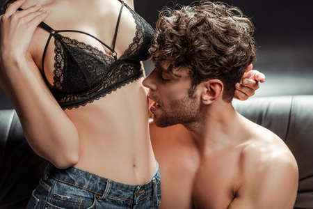 Handsome man kissing belly of sensual woman in bra on couch on black background