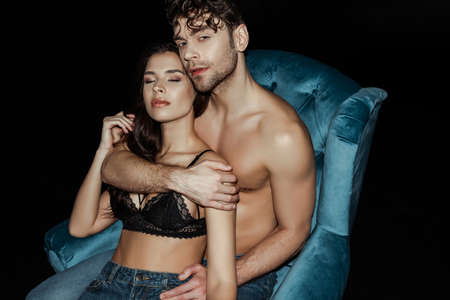 Handsome shirtless man embracing woman in bra on armchair isolated on black