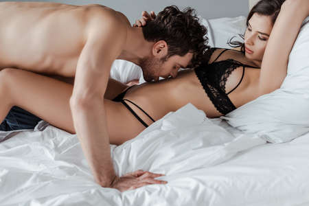 Handsome man kissing belly of sexy woman in underwear on bed Banque d'images