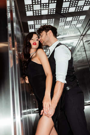 Selective focus of man undressing sexy woman in dress in elevator