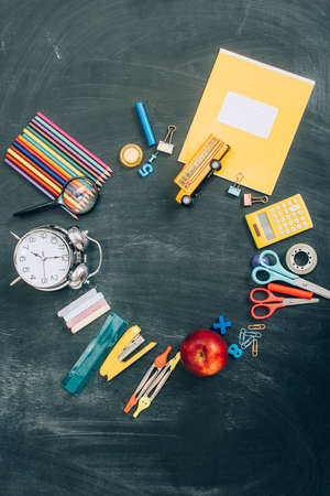 top view of frame with vintage alarm clock, whole apple and school supplies on black chalkboard with copy space Archivio Fotografico