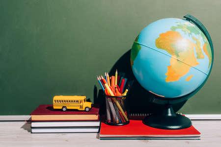 globe and pen holder on notebook near school bus model on books near green chalkboard