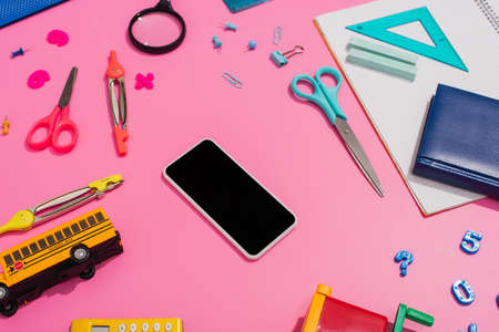 high angle view of smartphone with blank screen near school bus model and stationery on pink