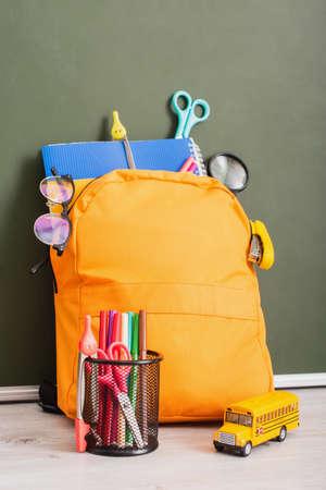 school backpack full of stationery near pen holder and school bus model