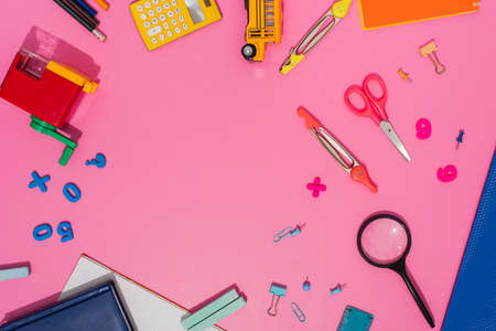 top view of school stationery and school bus model on pink with copy space