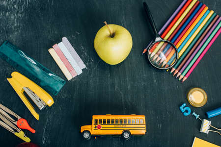top view of school bus model, whole apple and school stationery on black chalkboard