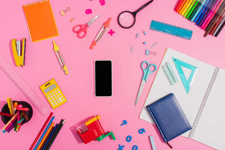top view of smartphone with blank screen surrounded by school supplies on pink