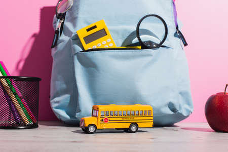 blue backpack with school supplies near school bus model, ripe apple and pen holder with felt pens on pink