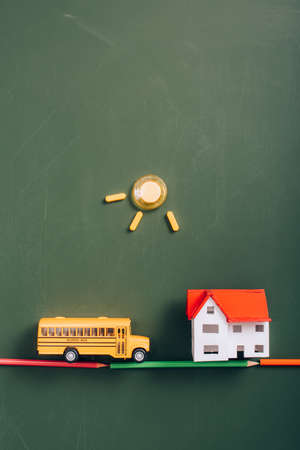 top view of toy school bus on road made of color pencils near house model, and sun made of magnets on green chalkboard