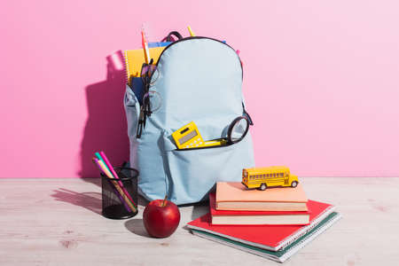 full backpack with school stationery near toy school bus on books, ripe apple and pen holder on pink