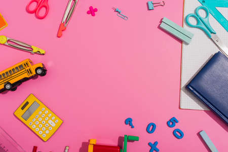 frame of multicolored school stationery on pink with copy space, top view