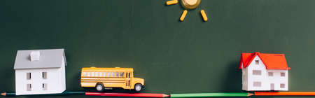 top view of toy school bus and house models on road made of color pencils, and sun made of magnets on green chalkboard, horizontal image 免版税图像