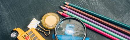 high angle view of magnifier, color pencils and school supplies on black chalkboard, panoramic shot