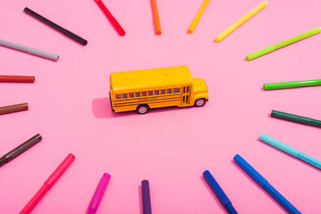high angle view of school bus model in frame of multicolored felt pens on pink 免版税图像