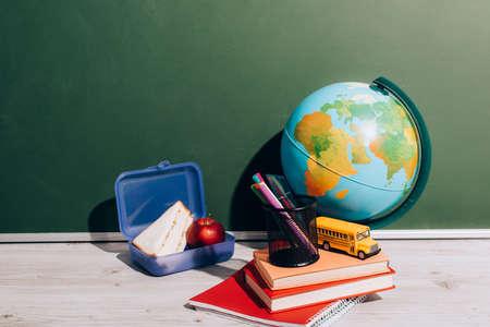 globe near lunch box, books, pen holder and school bus model one desk near green chalkboard 免版税图像