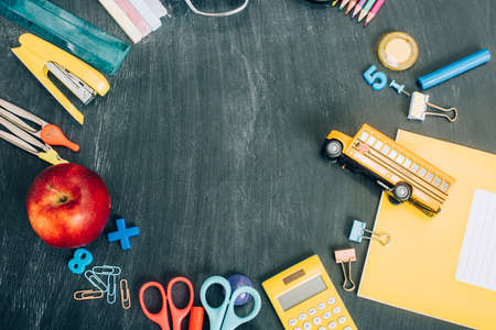 top view of frame with school bus model, ripe apple and school stationery on black chalkboard with copy space