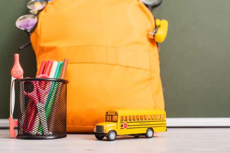 yellow backpack near school bus model, pen holder with felt pens, scissors and dividers on desk near green chalkboard 免版税图像