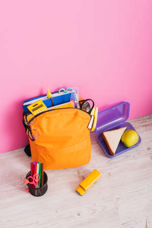 high angle view of backpack with school supplies near school bus model, lunch box and pen holder with felt pens and scissors on pink