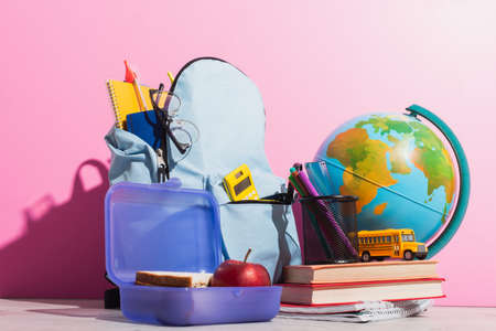 school backpack full of stationery near lunch box, globe, school bus model and books on pink 免版税图像