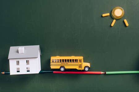 top view of yellow school bus on road made of color pencils, house model and sun made of magnets on green chalkboard