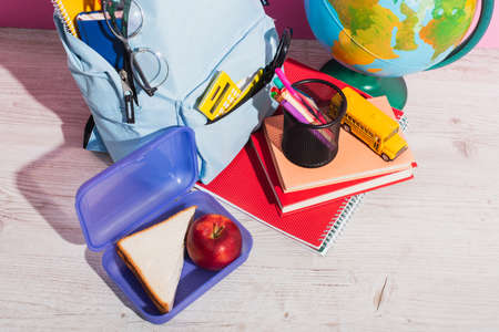 high angle view of blue backpack with school supplies near lunch box, globe, books, school bus model and apple on pink