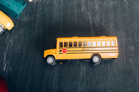 top view of yellow school bus model with stop sign on black chalkboard