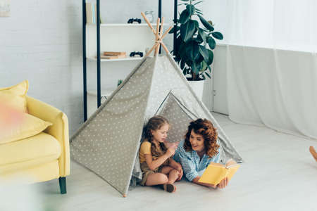 smiling babysitter reading book to adorable kid in play tent