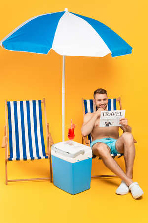 muscular man smiling while reading travel newspaper and sitting on deck chair near cocktail on portable fridge freezer on yellow