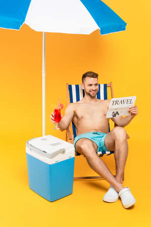 muscular man smiling while reading travel newspaper and holding cocktail near portable fridge freezer on yellow