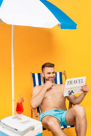 shirtless man smiling while reading travel newspaper and sitting on deck chair near cocktail on portable fridge freezer on yellow