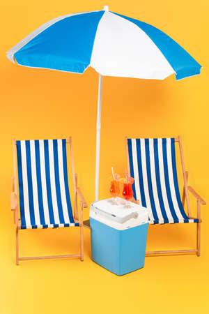 deck chair near beach umbrella and cocktails on portable fridge freezer on yellow