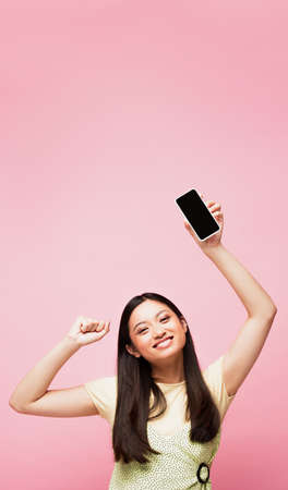 cheerful asian girl with clenched fist holding smartphone with blank screen isolated on pink