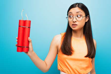 emotional asian girl in glasses holding dynamite sticks on blue Imagens
