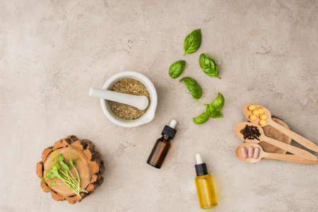 top view of herbs, green leaves, mortar with pestle, bottles and pills in wooden spoons on concrete background, naturopathy concept Stock fotó