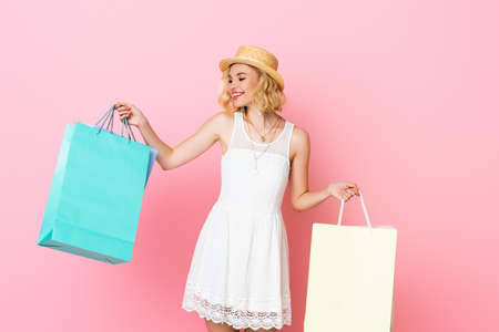 woman in straw hat and white dress holding shopping bags on pink Stock Photo