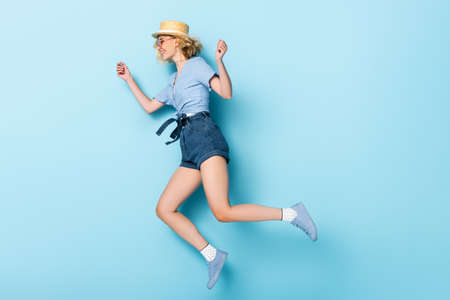 side view of young woman in straw hat and sunglasses jumping on blue