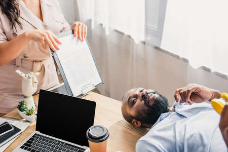 Selective focus of businesswoman blowing with clipboard on african amerian colleague suffering from heat in office Foto de archivo