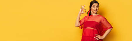horizontal image of pregnant woman in red tunic showing okay gesture while holding hand on hip on yellow