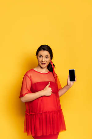 pregnant woman in red outfit showing thumb up while holding smartphone with blank screen on yellow Banco de Imagens