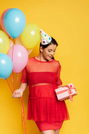 young pregnant woman in party cap holding colorful festive balloons and holding gift box on yellow