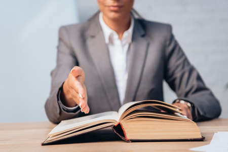 selective focus of lawyer in suit pointing with hand at book in office 免版税图像