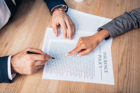 partial view of lawyer pointing with finger at insurance policy contract near businessman with pen