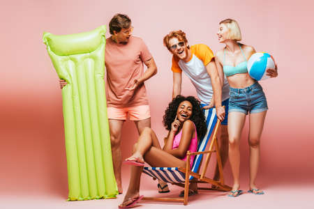 Yong multiethnic friends in swimsuits and sunglasses with inflatable ball and mattress on pink background