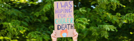 Panoramic orientation of man holding placard with i was hoping for a cooler death lettering with trees at background, ecology concept