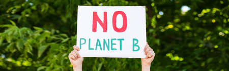 Horizontal crop of man holding placard with no planet b words with trees at background, ecology concept