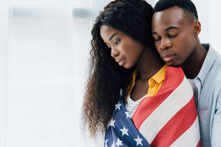 african american man with closed eyes near brunette woman covered with flag of america Stock Photo