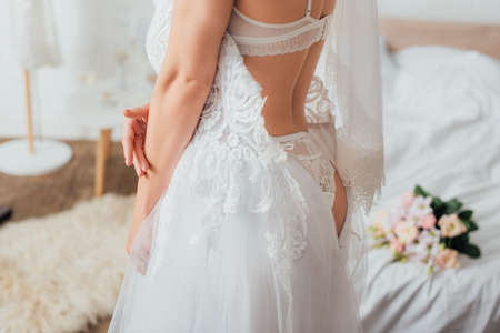Cropped view of bride in underwear and veil putting on lace wedding dress in bedroom