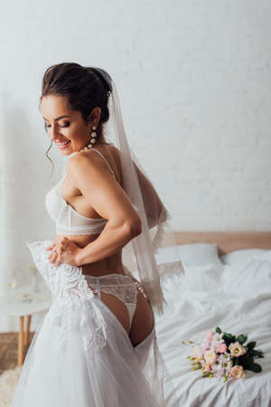 Young bride in lingerie and veil wearing wedding dress near bouquet on bed