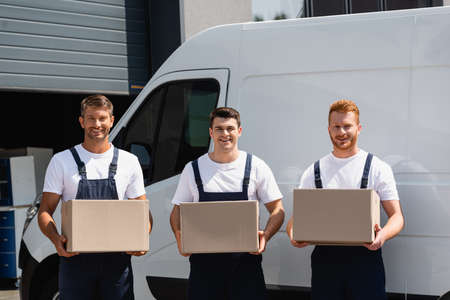 Movers in uniform looking at camera and holding cardboard boxes near truck on urban street